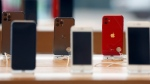 Rows of iPhones are displayed Saturday, March 14, 2020, inside a closed Apple store in downtown Brooklyn in New York.  (AP Photo/Kathy Willens)