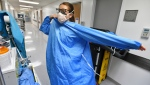 RN Zoe Zinis puts on fresh protective layers before entering the room of an infected patient in the COVID-19 ward at UF Health's downtown in Jacksonville, Fla., campus Friday, July 30, 2021. The second surge of COVID-19 infections in Jacksonville is stretching the capacity of area medical facilities to care for patients. (Bob Self/The Florida Times-Union via AP)