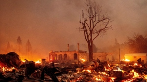Buildings burn as the Dixie Fire tears through the Greenville community of Plumas County, Calif., on Wednesday, Aug. 4, 2021. The fire leveled multiple historic buildings and dozens of homes in central Greenville. (AP Photo/Noah Berger)