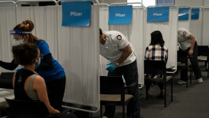 FILE - In this May 21, 2021, file photo, student nurse Dario Gomez, center, disinfects a chair after administering the Pfizer COVID-19 vaccine to a patient at Providence Edwards Lifesciences vaccination site in Santa Ana, Calif. (AP Photo/Jae C. Hong, File)