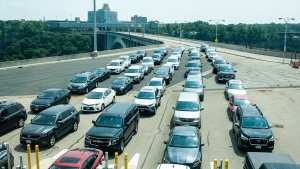 Cars wait on the Rainbow Bridge before crossing the border into Canada, in Niagara Falls, Ont. on Monday, August 9, 2021. American citizens and permanent residents are now allowed to enter Canada for non-essential purposes if they can provide proof that they've been fully vaccinated for at least 14 days.THE CANADIAN PRESS/Eduardo Lima