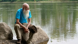 """David Lidstone, 81, sits for a photograph near the Merrimack River, Tuesday, Aug. 10, 2021, in Boscawen, N.H. Lidstone, an off-the-grid New Hampshire hermit known to locals as """"River Dave,"""" had been living in a cabin in the woods along the Merrimack River, in Canterbury, N.H., for nearly three decades. He was jailed July 15, 2021 on a civil contempt sanction and was told he'd be released if he agreed to leave the cabin, that has since burnt down. (AP Photo/Steven Senne)"""