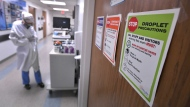 Signs on all the patient doors remind staff and visitors of precautions to prevent the spread of the Coronavirus in the COVID-19 ward at UF Health's downtown in Jacksonville, Fla., campus Friday, July 30, 2021. (Bob Self/The Florida Times-Union via AP)