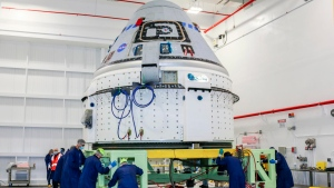 In this June 2, 2021 photo made available by NASA, technicians prepare Boeing's CST-100 Starliner for the company's Orbital Flight Test-2 (OFT-2) in the Commercial Crew and Cargo Processing Facility at NASA's Kennedy Space Center in Florida. On Friday, Aug. 13, 2021, Boeing and NASA officials said the capsule is grounded for months and possibly even until next year because of a vexing valve problem. (NASA via AP)