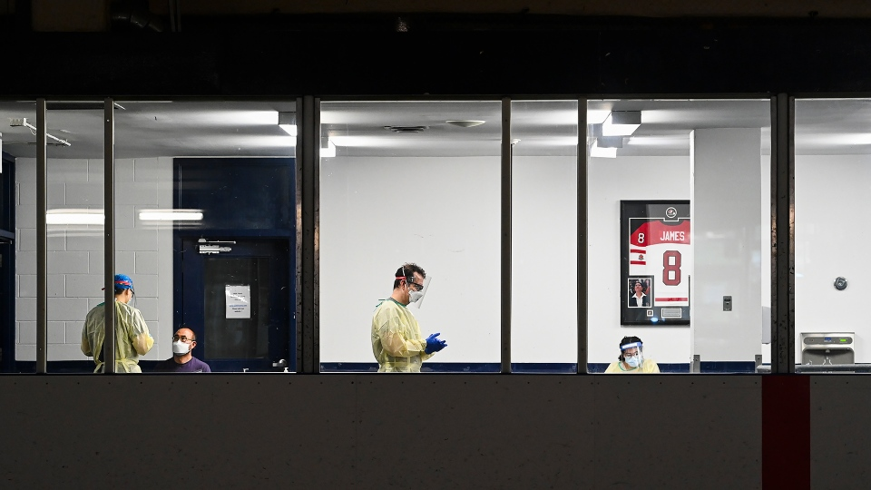 Health-care workers get ready to test a person at a pop-up COVID-19 assessment centre at the Angela James Arena during the COVID-19 pandemic in Toronto May 19, 2021. THE CANADIAN PRESS/Nathan Denette
