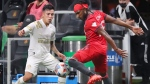 Atlanta United midfielder Ezequiel Barco has his long drive blocked by Toronto FC forward Ifunanyachi Achara before getting off a shot during the second half of an MLS soccer match Wednesday, Aug. 18, 2021, in Atlanta. (Curtis Compton/Atlanta Journal-Constitution via AP)