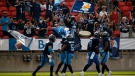 Fans celebrate with the team as Toronto Argonauts players score a touchdown during first half CFL football action against the Winnipeg Blue Bombers, in Toronto, Saturday, Aug. 21, 2021. THE CANADIAN PRESS/Cole Burston
