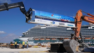 In this Friday, Jan. 29, 2021 photo, The Carnival Dream cruise ship arrives as construction work is underway for Carnival Cruise Line's new Terminal F, which will be the homeport to the Carnival Celebration cruise ship at PortMiami, in Miami. Cruise companies are adapting to a changing landscape amid a rise in COVID-19 cases that is threatening to dampen the industry's comeback.(AP Photo/Lynne Sladky)