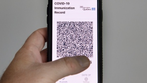 A woman looks at the Quebec government's new vaccine passport called VaxiCode on a phone in Montreal, Wednesday, August 25, 2021, as the COVID-19 pandemic continues in Canada and around the world. THE CANADIAN PRESS/Graham Hughes