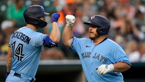 Toronto Blue Jays' Alejandro Kirk, right, is greeted by Corey Dickerson (14) after hitting a solo home run during the sixth inning of a baseball game against the Detroit Tigers, Saturday, Aug. 28, 2021, in Detroit. (AP Photo/Carlos Osorio)