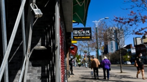 People walk past businesses on Spadina Avenue in Chinatown in Toronto, Thursday, May 13, 2021. Ontario's stay-at-home order lifts today but most other public health measures are staying in place. THE CANADIAN PRESS/Nathan Denette