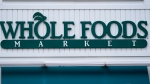 The Whole Foods Market logo is shown on the front of a store, Wednesday, July 14, 2021, in Cambridge, Mass. Amazon, which owns the grocery chain, said Wednesday, Sept. 8, that it will bring its cashier-less technology to two Whole Foods stores for the first time, letting shoppers grab what they need and leave without having to open their wallets. (AP Photo/Charles Krupa)