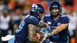 Toronto Argonauts quarterback Nick Arbuckle (9) hands the ball off to running back D.J. Foster (29) in the first half of their CFL football game against the Hamilton Tiger-Cats in Toronto, Friday, Sept. 10, 2021. THE CANADIAN PRESS/Cole Burston