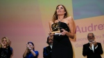Audrey Diwan holds the Golden Lion award for 'Happening' onstage at the closing ceremony during the 78th edition of the Venice Film Festival in Venice, Italy, Saturday, Sept. 11, 2021. (AP Photo/Domenico Stinellis)