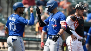 Toronto Blue Jays' Lourdes Gurriel Jr. right, is congratulated by Marcus Semien after hitting a grand slam against the Baltimore Orioles in the first inning of a baseball game Sunday, Sept. 12, 2021, in Baltimore. (AP Photo/Gail Burton)
