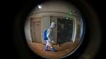 This photo taken through a door pinhole shows a medical worker wearing a protective clothing disinfectants a corridor of a hotel used for foreigners to stay during a period of health quarantine in Shanghai, China, Thursday, Aug. 12, 2021. More than 30 Chinese officials have been fired or received other punishments over accusations they failed to respond properly to the latest surge of the coronavirus in the country. (AP Photo/Andy Wong)