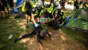 Toronto police make arrests as they clear the Lamport Stadium Park encampment in Toronto on Wednesday July 21, 2021. The operation came a day after a different encampment was cleared at a downtown park. The city has cited the risk of fires and the need to make parks accessible to everyone as factors behind the clearings. THE CANADIAN PRESS/Chris Young