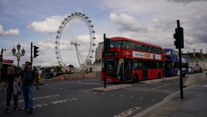 A double decker bus drives on Westminster Bridge, against the backdrop of the LondonEye, in London, Friday, Sept. 17, 2021.(AP Photo/Alberto Pezzali)