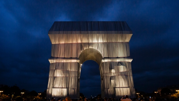 """The wrapped Arc de Triomphe monument is pictured on Saturday, Sept. 18, 2021, in Paris. The """"Arc de Triomphe, Wrapped"""" project by late artist couple Christo and Jeanne-Claude is on view until Oct. 3. Visitors to the famous Napoleonic arch, which dominates the Champs-Elysees Avenue, will not only be able to see the gleaming silver and blue fabric, but to touch it too — as the artists had intended. (AP Photo/Lewis Joly)"""