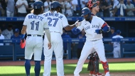 Toronto Blue Jays' Teoscar Hernandez, right, celebrates with Bo Bichette (11) and Vladimir Guerrero Jr. (37) after hitting a three-run home run in the fourth inning of an American League baseball game against the Minnesota Twins in Toronto on Saturday, Sept. 18, 2021. THE CANADIAN PRESS/Jon Blacker