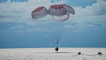 In this image taken provided by SpaceX, a capsule carrying four people parachutes into the Atlantic Ocean off the Florida coast, Saturday, Sept. 18, 2021. The all-amateur crew was the first to circle the world without a professional astronaut. (SpaceX via AP)