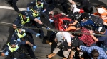 Victoria police fire pepper spray during a clash with protesters at a Rally for Freedom in Melbourne, Australia, Saturday, Sept. 18, 2021. The protesters were demonstrating against the latest COVID-19 lockdown in Melbourne. (James Ross/AAP Image via AP)