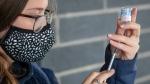 Georgia Mates, prepares a Moderna COVID-19 vaccine ahead of a drive-thru clinic at Richardson stadium in Kingston, Ont., on Friday, Jul. 2, 2021. THE CANADIAN PRESS/Lars Hagberg