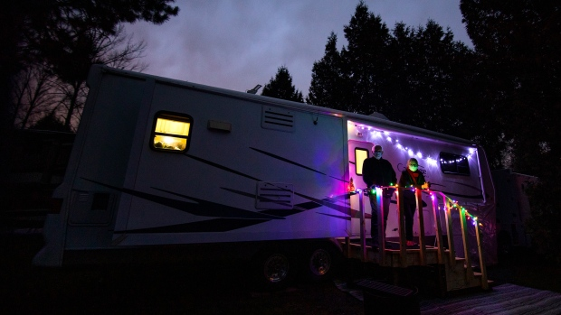 Paul Funston and Mary Lou Baldwin pose for a photo with their trailer in Fort Langley, B.C., Friday, December 18, 2020. The duo would normally spend the winter south of the border, but with the Canada-U.S border closed due to the COVID-19 pandemic, they are spending it at a campground in southern B.C.  THE CANADIAN PRESS/Marissa Tiel