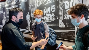 Jimmy Staveris, left, manager of Dunn's Famous restaurant scans the COVID-19 QR code of a client in Montreal, Wednesday, September 1, 2021, as the Quebec government's COVID-19 vaccine passport comes into effect. THE CANADIAN PRESS/Graham Hughes