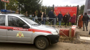 People stand behind the fence near the Perm State University with the a Rosguardia (National Guardia) on the left, in Perm, Russia, Monday, Sept. 20, 2021. (AP Photo/Anastasia Yakovleva)
