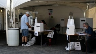 People vote outdoors under a tent at a polling location in a church parking lot on election day during the 44th Canadian general election in Ottawa, on Monday, Sept. 20, 2021. THE CANADIAN PRESS/Justin Tang