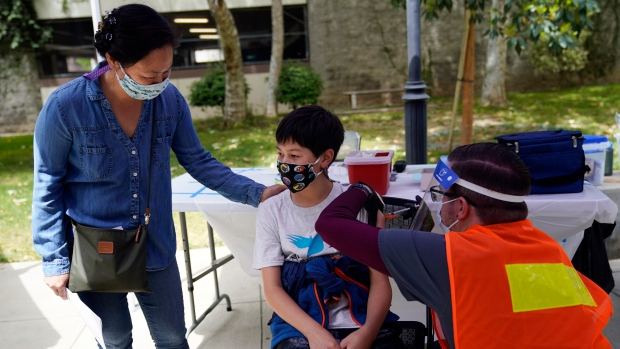 Colin Sweeney, 12, gets a shot of the Pfizer COVID-19 vaccine as his mother Nicole pats his shoulder at the First Baptist Church of Pasadena, Friday, May 14, 2021, in Pasadena, Calif. (AP Photo/Marcio Jose Sanchez)