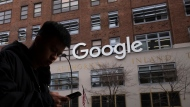 FILE - In this file photo dated Monday, Dec. 17, 2018, a man using a mobile phone walks past Google offices in New York. Google is planning to buy New York's St. John's Terminal for $2.1 billion, making it the anchor of its Hudson Square campus. Alphabet and Google Chief Financial Officer Ruth Porat said Tuesday, Sept. 21, 2021, that the company is looking to invest more than $250 million in its New York campus this year. (AP Photo/Mark Lennihan, FILE)