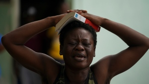 A migrant from Haiti prays with a bible on her head during a Mass at an improvised refugee shelter in Ciudad Acuña, Tuesday, Sept. 21, 2021. The options remaining for thousands of Haitian migrants straddling the Mexico-Texas border are narrowing as the United States government ramps up to an expected six expulsion flights to Haiti, and Mexico began busing some away from the border. (AP Photo/Fernando Llano)