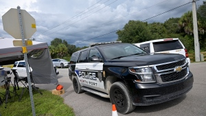 """North Port Police vehicles leave the Carlton Reserve during a search for Brian Laundrie, Tuesday, Sept. 21, 2021, in Venice, Fla. Laundrie is a person of interest in the disappearance of his girlfriend, Gabrielle """"Gabby"""" Petito. (AP Photo/Phelan M. Ebenhack)"""
