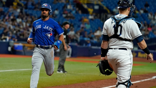 Toronto Blue Jays' Marcus Semien scores past Tampa Bay Rays catcher Mike Zunino (10) on a sacrifice fly by Bo Bichette during the sixth inning of a baseball game Tuesday, Sept. 21, 2021, in St. Petersburg, Fla. (AP Photo/Chris O'Meara)