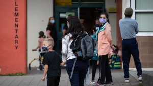 Wearing face masks to curb the spread of COVID-19, Karin Brodbeck drops her son Ricardo Brodbeck, 6, a Grade 1 student, off at Lynn Valley Elementary School in North Vancouver, B.C., Thursday, Sept. 9, 2021. THE CANADIAN PRESS/Darryl Dyck