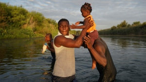 Men carry a little girl across the Rio Grande river as migrants, many from Haiti, leave Del Rio, Texas, to return to Ciudad Acuna, Mexico, early Wednesday, Sept. 22, 2021, to avoid possible deportation from the U.S. (AP Photo/Fernando Llano)