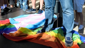 In this Sunday, Aug. 16, 2020 file photo, a man stands on a Rainbow Flag as he attends a demonstration of far-right activists against LGBT rights in Warsaw, Poland. A rural region in southern Poland has revoked an anti-LGBT resolution under the threat of losing European Union funding. The regional assembly of Swietokrzyskie voted in a special session on Wednesday, Sept. 22, 2021 to revoke the resolution, first passed in 2019. (AP Photo/Czarek Sokolowski, file)