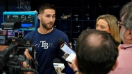 Tampa Bay Rays' Kevin Kiermaier, left, talks to reporters before a baseball game against the Toronto Blue Jays Wednesday, Sept. 22, 2021, in St. Petersburg, Fla. Kiermaier was answering questions about him picking up the Blue Jays pitch data card after being tagged out at home plate by catcher Alejandro Kirk during Monday's game. (AP Photo/Chris O'Meara)