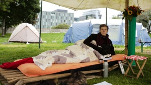 Climate activist Henning Jeschke, who is since 24 days on a hunger strike, lays on a mattress under a tent in a small camp of climate activists as he poses for a photo in Berlin, Wednesday, Sept. 22, 2021. With his hunger strike he hopes to pressure candidates for chancellor of Germany into meeting him for a debate about the climate crisis ahead Sunday's general election. For the first time in Germany's history, climate change is a central issue of an election campaign, overwhelmingly so for the young generation. (AP Photo/Markus Schreiber)