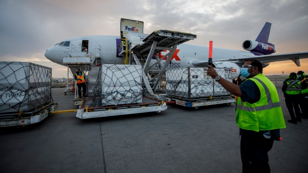 Workers unload a shipment of the Moderna COVID‑19 vaccine at the FedEx hub at Pearson International Airport in Toronto on Thursday, May 20, 2021. THE CANADIAN PRESS/Cole Burston