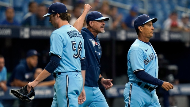 Toronto Blue Jays manager Charlie Montoyo, right, and pitching coach Pete Walker, center, run onto the field after starting pitcher Ryan Borucki, left, was ejected after hitting Tampa Bay Rays' Kevin Kiermaier with a pitch during the eighth inning of a baseball game Wednesday, Sept. 22, 2021, in St. Petersburg, Fla. (AP Photo/Chris O'Meara)