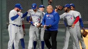 Toronto Blue Jays left fielder Lourdes Gurriel Jr., second from front left, heads to the dugout with a trainer and a towel-wrapped hand after he was injured fielding a double by Minnesota Twins' Mitch Garver in the fifth inning of a baseball game, Thursday, Sept. 23, 2021, in Minneapolis. (AP Photo/Jim Mone)