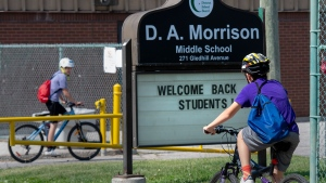 Kids ride their bikes past the sign for D.A. Morrison school in Toronto on Wednesday June 2, 2021. Ontario Premier Doug Ford announced Wednesday that Ontario students won't return to class until September.  THE CANADIAN PRESS/Frank Gunn