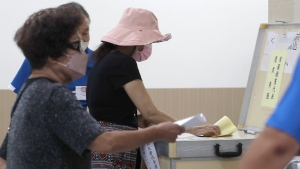 Members of the Nationalist Party, or KMT, cast their ballot for election of its party chairman at a polling station in Taipei, Taiwan, Saturday, Sept. 25, 2021. Fraught relations with neighboring China are dominating Saturday's election for the leader of Taiwan's main opposition Nationalist Party. (AP Photo/Chiang Ying-ying)