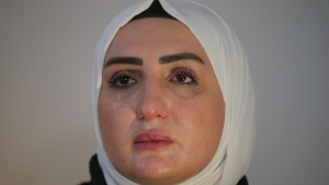 """Fatima Alzahra Shon, 32, a Syrian refugee cries during an interview with The Associated Press in Istanbul, Friday, Sept. 17, 2021. Fatima Alzahra Shon thinks neighbors attacked her and her son in their Istanbul apartment building because she is Syrian. The 32-year-old refugee from Aleppo was confronted on Sept. 1 by a Turkish woman who asked her what she was doing in """"our"""" country. Shon replied, """"Who are you to say that to me?"""" The situation quickly escalated.(AP Photo/Emrah Gurel)"""