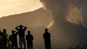 Residents look from a hill as lava continues to flow from an erupted volcano, on the island of La Palma in the Canaries, Spain, Friday, Sept. 24, 2021. A volcano in Spain's Canary Islands continues to produce explosions and spew out lava, five days after it erupted. Two rivers of lava continue to slide slowly down the hillside of La Palma on Friday. (AP Photo/Emilio Morenatti)