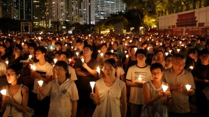 FILE- Tens of thousands of people attend a candlelight vigil at Victoria Park in Hong Kong on June 4, 2016, to commemorate victims of the 1989 military crackdown in Beijing. The group, Hong Kong Alliance in Support of Patriotic Democratic Movements of China, that had organized annual vigils in remembrance of victims of the Chinese military's crushing of the 1989 Tiananmen Square pro-democracy protests voted to disband Saturday, Sept. 25, 2021 amid an ongoing crackdown on independent political activism in the semi-autonomous Chinese city. (AP Photo/Kin Cheung)