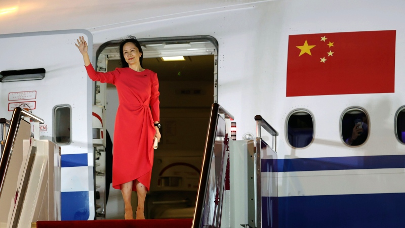 In this photo released by China's Xinhua News Agency, Huawei CFO Meng Wanzhou waves as she steps out of an airplane after arriving at Shenzhen Bao'an International Airport in Shenzhen in southern China's Guangdong Province, Saturday, Sept. 25, 2021. A top executive from global communications giant Huawei Technologies returned to China on Saturday following what amounted to a high-stakes prisoner swap with Canada and the U.S. (Jin Liwang/Xinhua via AP)